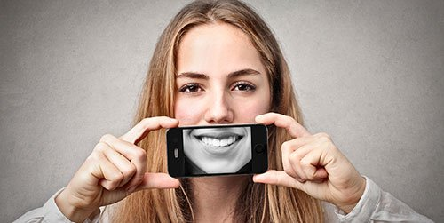 Woman holding up picture of smile