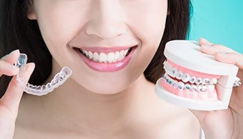Woman comparing Invisalign and regular braces