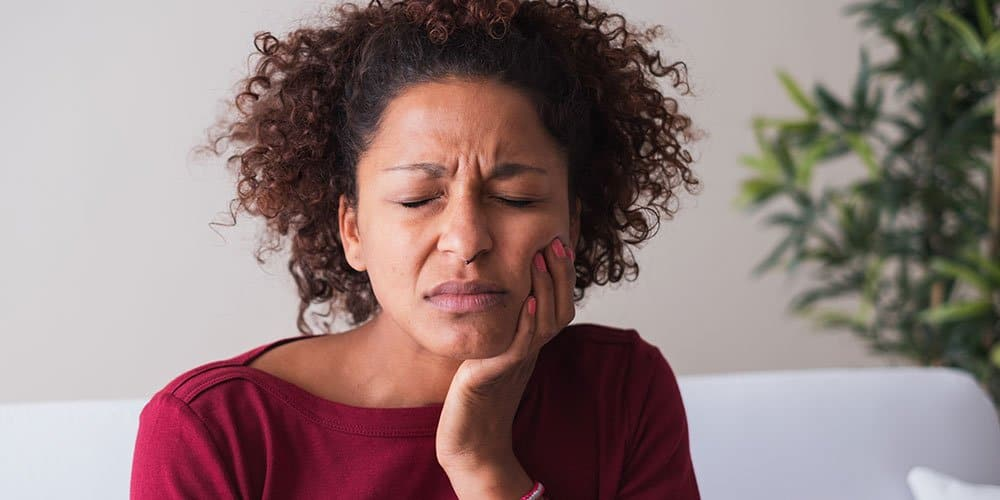 Woman with gum disease holding sore jaw