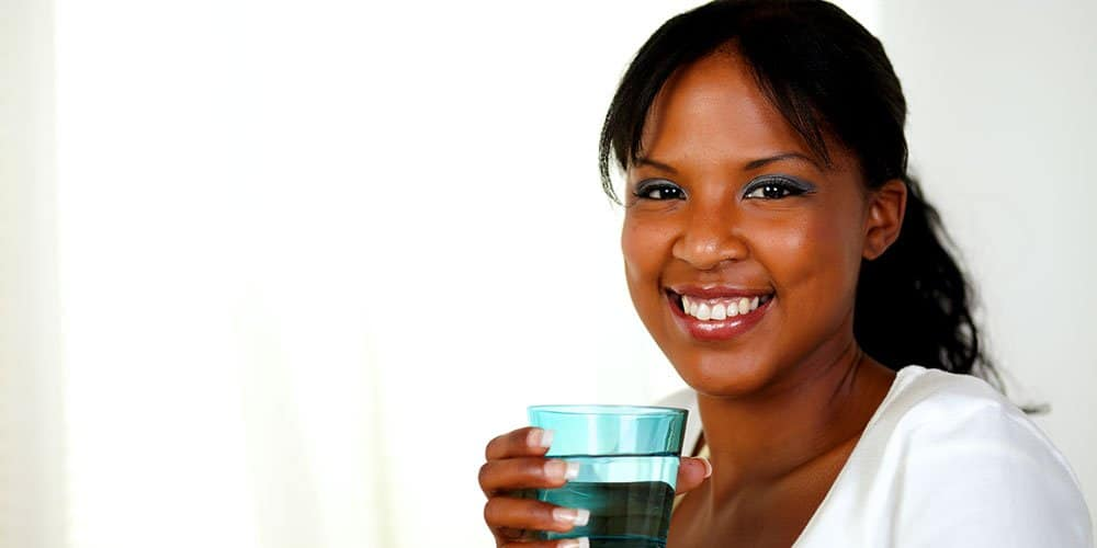 Smiling woman drinking a glass of tap water